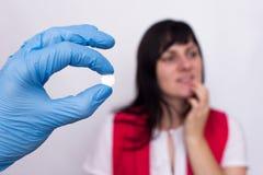 Medico tiene una pillola in sua mano da herpes orale, la ragazza tiene il suo labbro, pillole contro herpes, erba medica immagini stock libere da diritti