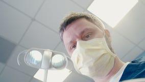 Medico in una maschera sta avvicinandosi a al paziente ed all'ambulatorio d'inizio in odontoiatria video d archivio