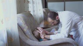 Medico visita un bambino malato a casa Gola ispezionata, gola irritata archivi video
