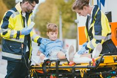 Medics putting injured boy on stretcher after accident. In front of ambulance car Royalty Free Stock Image