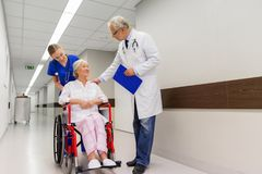 Medics and senior patient in wheelchair at clinic Royalty Free Stock Photos