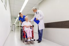 Medics and senior patient in wheelchair at clinic Stock Image