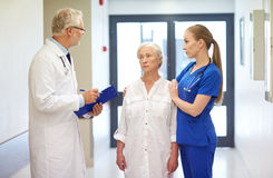 Medics and senior patient woman at hospital Stock Photo