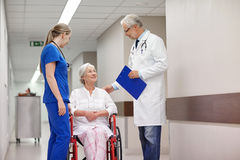 Medics and senior woman in wheelchair at hospital Stock Photos