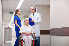 Medics and senior woman in wheelchair at hospital Royalty Free Stock Image