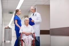 Medics and senior woman in wheelchair at hospital Royalty Free Stock Image