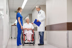 Medics and senior woman in wheelchair at hospital Royalty Free Stock Photography