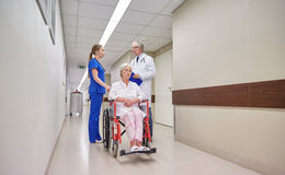 Medics and senior woman in wheelchair at hospital Stock Image