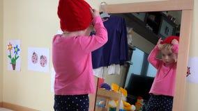Medida bonito dos chapéus da menina na frente do espelho em casa vídeos de arquivo