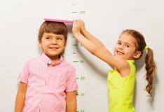 A medida da altura do menino e da menina pela parede escala em casa Fotos de Stock Royalty Free