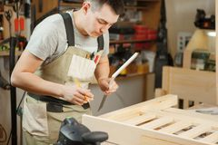 Medida da distância do artesão entre pranchas de madeira com ajuda da régua Foto de Stock