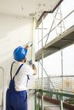 Medida da distância Trabalhe no local, trabalhador na alta altitude no andaime Imagens de Stock