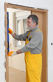 Medida da verticalidade do construtor da porta com ferramenta nivelada Fotografia de Stock
