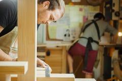 Medida das pranchas de madeira do artesão com régua Carpinteiro na oficina Foto de Stock
