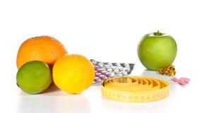 Medida de fita, comprimidos da dieta e frutas Imagem de Stock Royalty Free