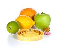 Medida de fita, comprimidos da dieta e frutas Imagens de Stock Royalty Free