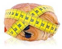 Medida de fita em torno do croissant Fotos de Stock Royalty Free
