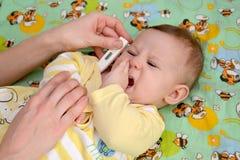 Medida de la temperatura al bebé gritador enfermo el termómetro electrónico fotografía de archivo