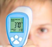 Medida de la temperatura del cuerpo por el termómetro infrarrojo imagen de archivo