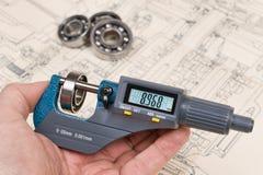 Medida de los rodamientos Indicador de tornillo de micrómetro en mano humana imágenes de archivo libres de regalías