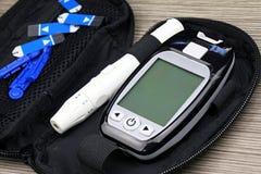 Medida do açúcar no sangue, jogo do diabético, pena da seringa com insulina e glucometer fotografia de stock