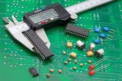 Medida electrónica IC del calibrador y componente electrónico en el PWB verde fotos de archivo