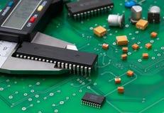 Medida eletrônica de IC do compasso de calibre e parte eletrônica no PWB verde imagens de stock
