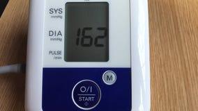 Medida hecha en casa de la presión arterial usando el sphygmomanometer electrónico almacen de metraje de vídeo