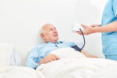 Medidas del cuidador la presión arterial de un viejo hombre foto de archivo