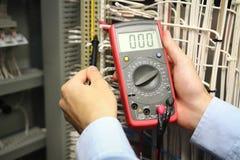 Medidas del electricista con el probador del multímetro fotos de archivo