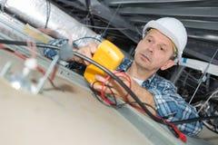 Medidas do eletricista com voltímetro fotos de stock royalty free