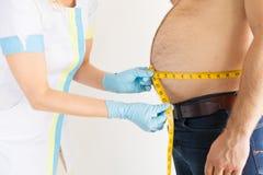 Medidas gordas do est?mago do homem de medi??o da dietista durante o controle fotos de stock