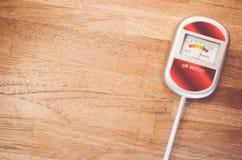 medidor de pH análogo del suelo en una superficie de madera Fotografía de archivo libre de regalías