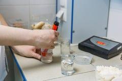 Medidor de pH del uso del científico en laboratorio en la fábrica de la comida para el producto del control y del análisis Produc imágenes de archivo libres de regalías