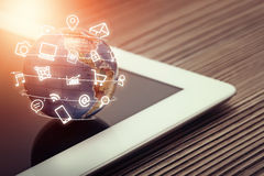 Medienikonen fliegen um Kugel auf Tablet-Computer Lizenzfreie Stockfotos