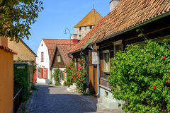 Medieval alley in Visby, Sweden. Medieval alley in the historic Hanse town Visby, Sweden. The gunpowder tower of the medieval city wall is visible in the Stock Image