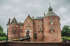 Medieval Ammersoyen Castle with its brick towers, wooden bridge and green garden on cloudy day. Near to the historic and vibrant city of s-Hertogenbosch royalty free stock photos