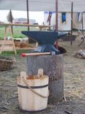 Medieval anvil. A medieval anvil sitting on a stump, behind a wooden bucket Royalty Free Stock Photography