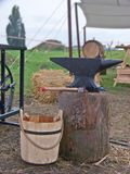 Medieval anvil. A medieval anvil sitting on a stump, near a wooden bucket Royalty Free Stock Image