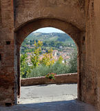 Medieval Arch in Tuscany. Medieval arch in the town of Certaldo Italy with typical Tuscan landscape showing through arch royalty free stock images