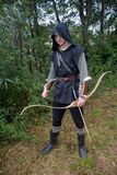 Medieval archer with black hood and coloured arrows in the quiver stands with arrow Stock Photos