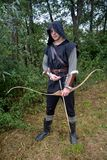 Medieval archer with black hood and coloured arrows in the quiver stands with arrow Royalty Free Stock Photography