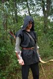 Medieval archer with black hood and coloured arrows in the quiver stands with bow Royalty Free Stock Photo