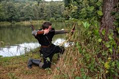 Medieval archer with black hood kneels at the side on the ground before a lake, aims with arrow and curve aside Royalty Free Stock Images