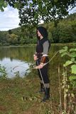 Medieval archer with black hood stands with tense curve and arrow on water Royalty Free Stock Images