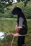 Medieval archer with black hood stands with tense curve and arrow on water Stock Images