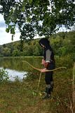 Medieval archer with black hood stands with tense curve and arrow on water Stock Photography