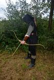Medieval archer of the side stands with black hood and with tense bow and with arrow Stock Images
