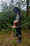 Medieval archer of the side stands with black hoodie and with tense curve and with arrow Royalty Free Stock Image