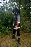 Medieval archer of the side stands with black hoodie and with tense curve and with arrow Stock Photo